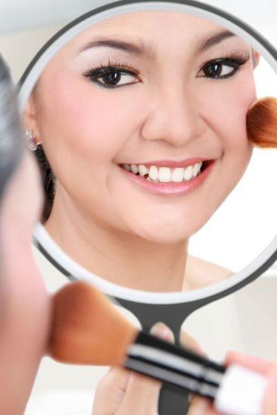 femme asiatique se poudrant le teint en se regardant dans un miroir