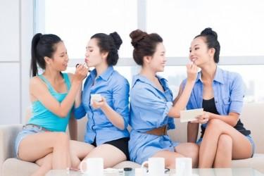 4 jeunes filles qui se maquillent en s'amusant sur un canapé