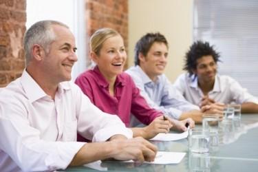 groupe d'hommes et femmes souriants réunis autour d'une table