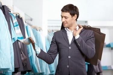 homme touche des vêtements en boutique