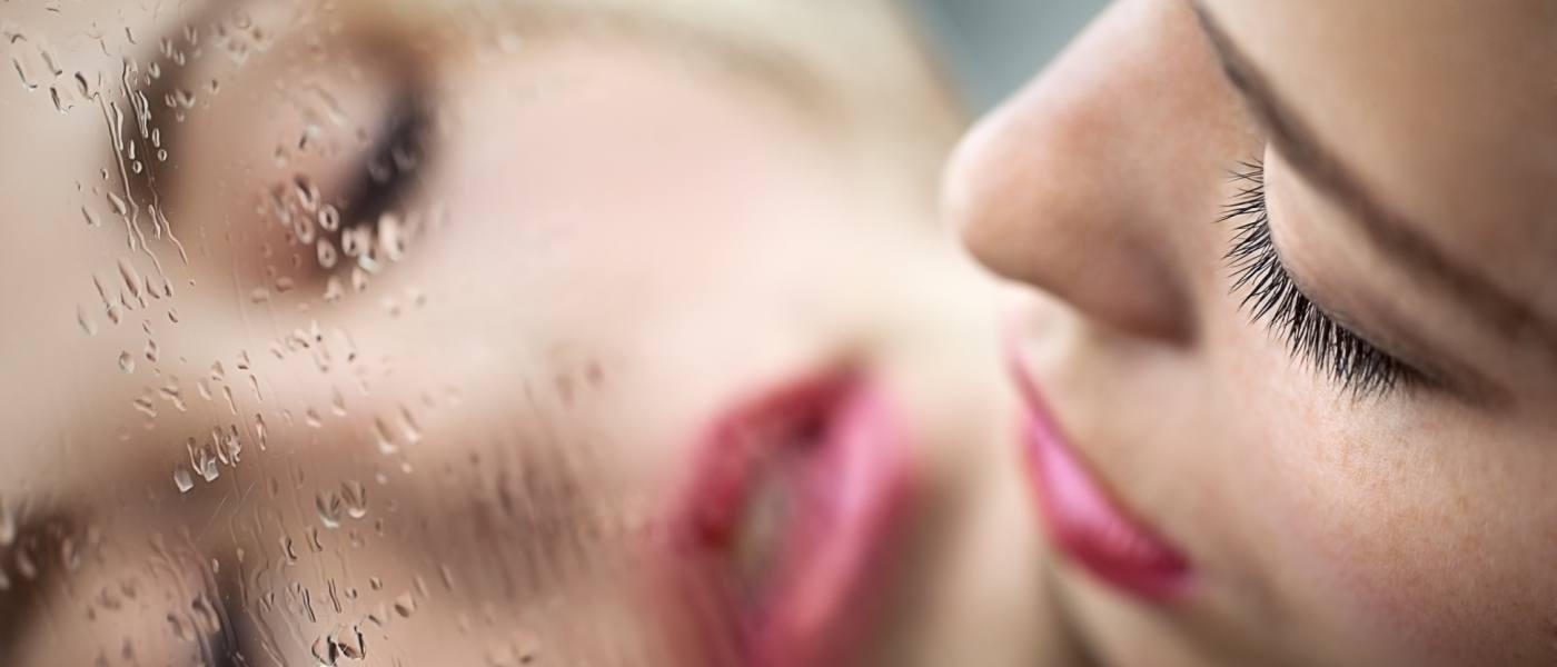 reflet du visage d'une femme dans un miroir avec de la buée