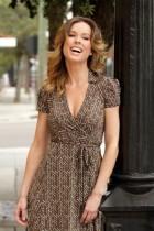 femme souriante portant une robe portefeuille marron