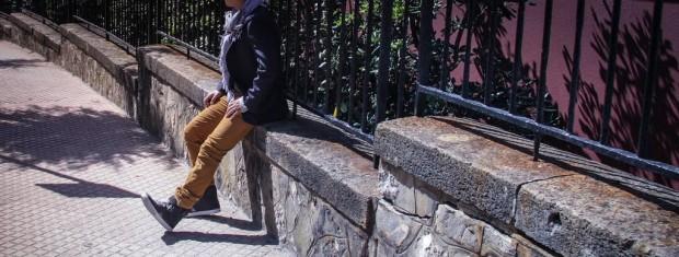 Homme avec un pantalon moutarde assis sur un muret