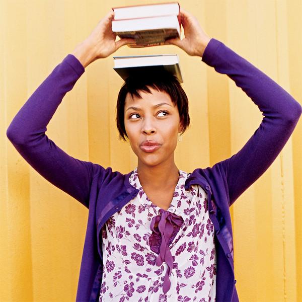 Une jolie jeune femme en tenue violette porte des livres sur sa tête